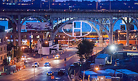 """The illuminated artwork """"The """"H"""" in Harlem"""" is seen hanging under the 125th Street viaduct in Harlem in New York on Tuesday, July 1, 2014. The aluminum truss structure with 30 LED fixtures attached and illuminated by plasma lighting was designed by lighting designer and artist Bentley Meeker. The sculpture will remain on view until September 25. (© Richard B. Levine)"""