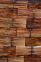 Stacked red cedar shingles.  H and L Salvage buys timber (what is left after a company clear cuts and leaves), and they make red cedar shakes and cut boards.  Keith and Desiree Landers and daughter Carmen live beside the mill on Goose Creek.  Desirsee cuts shingles--probably the only woman to do this.  Nathan Kinsman and Jake Howell split cedar for shakes.  Jack and Don Hays (red) separate wood that Keith cuts with his saw..Thorne Bay on Prince of Wales Island has a population of 495.  It was founded as a logging camp in the '60s.  Much of its economy is based on the timber industry, but today they are more dependent on sport fishing.  ..