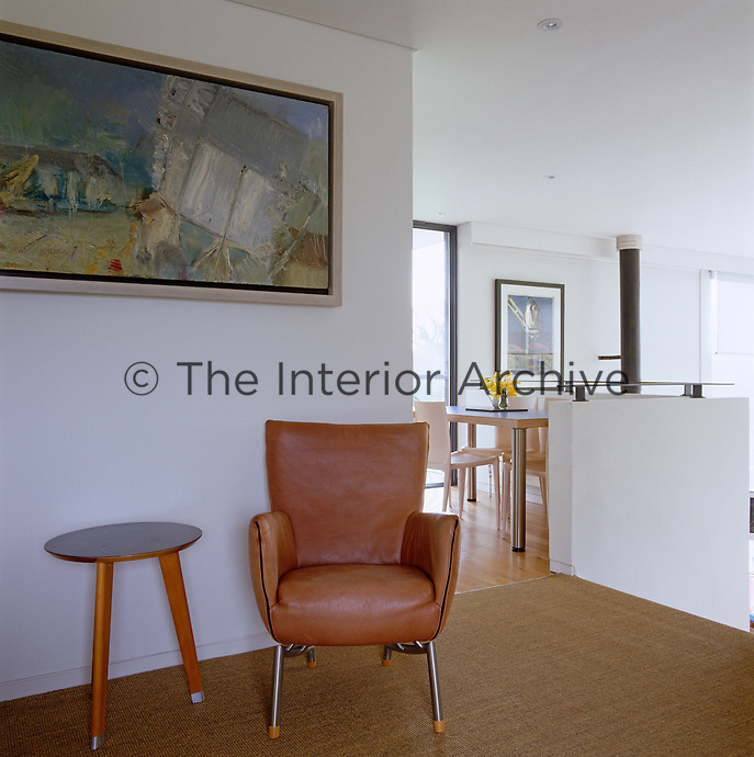 On the landing a 50's style leather chair stands next to a side table from Purves and Purves