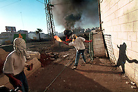 intifada. A Palestinian youth throws a molotow cocktail at soldiers from Israeli army on the outskirts of Ramallah.