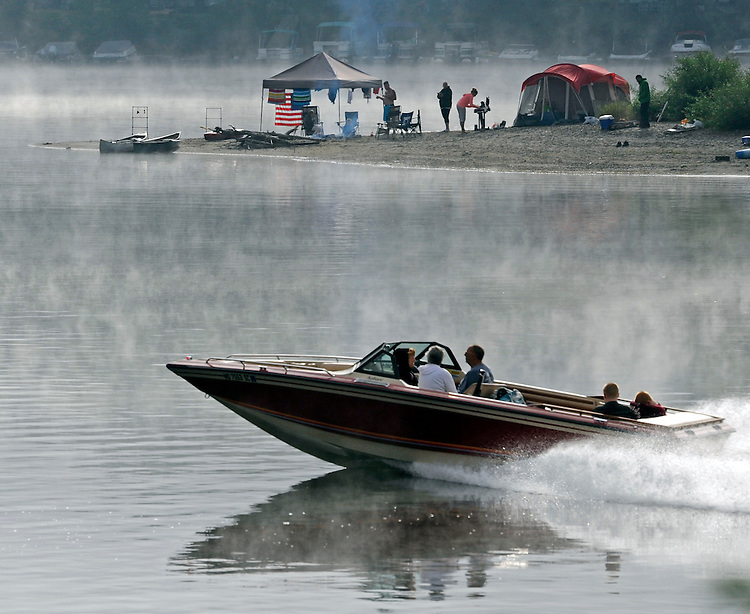 Campers cook breakfast on Mitch's Island as a boat cuts through fog on the Connecticut River between Hadley and Northampton, Mass., on Sunday, September 06, 2015. Photo by Christopher Evans