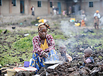 A woman cooks a meal for her children after being displaced in October 2008 by fighting between forces of rebel Tutsi General Laurent Nkunda and the Congolese government. They took refuge with dozens of other families in a church and adjacent school in the Goma neighborhood of Musawato.  A quarter of a million people have been newly displaced by fighting in the eastern Congo, where some 5.4 million have died since 1998 from war-related violence, hunger and disease.