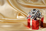 Red gift box with a silver bow on golden background
