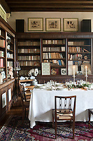 The dining room is lined with bespoke wooden bookcases and the table has been laid for Christmas dinner