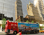 NYC, New York, U.S.  21st May 2013.  A colorful sightseeing bus passes by reflection of ornate building reflected in the vast window facade of an office building, during a pleasant spring day, with a high of 86ºF/32ºC in Manhattan.