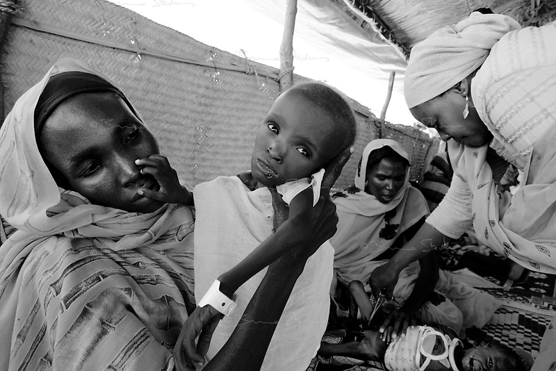Kalma IDP camp, South Darfur, August 3, 2004.Sharif Adam, 12 months old, on his mother lap. He suffers from severe malnutrition, weighing at only 4,3 kg . He is one of about 2000 children in the MSF emergency nutrition program in this camp.