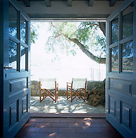 View through open doors to a pair of director's chairs sitting on the terrace