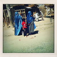 Two burqa clad woman with a child wait to cross the street.