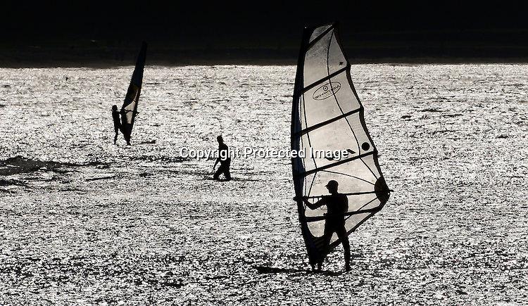 A windsurfer was silhouetted by the sun off the coast of Crissy Field in the Presido as the weather and the wind was perfect on the bay in San Francisco, California.