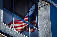 The U.S. flag waves in reflection in a second floor window.