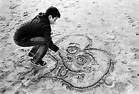 France. Alpes-Maritimes. Cannes. Nicola Ruef is drawing a heart on the beach's sand. 2.11.10. MODEL RELEASED. © 2010 Didier Ruef
