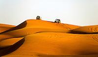 Four wheel drive vehicles  drive in the desert. Dubai. United Arab Emirates.