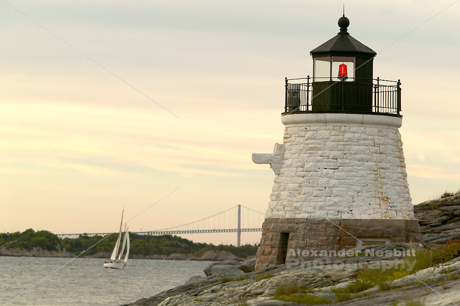 USA, Newport, RI - Castle Hill light house at the mouth of Narragansett Bay with Schooner Madeline sailing past.