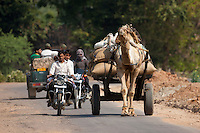 Indian men on motorbikes and camel cart in Sawai Madhopur in Rajasthan, Northern India