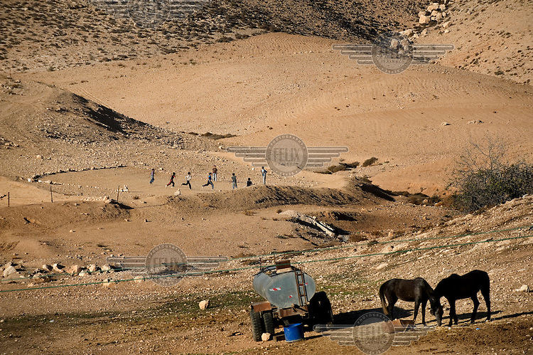 Two horses graze in front of a group of children playing football in the Arab village of Darajat, in Israel's Negev desert..
