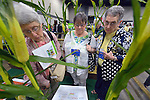 """Three women make their way through """"The Field,"""" a display that explores social issues related to agriculture, during at the United Methodist Women Assembly in the Kentucky International Convention Center in Louisville, Kentucky, on April 25, 2014."""
