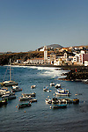 Boats at anchor in the harbour with the Cathedral, waves and black sandy beach of Candelaria in the background. Candelaria, Tenerife, Canary Islands, Spain.