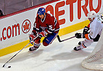 3 February 2007: Montreal Canadiens defenseman Mathieu Dandenault (25) keeps the puck away from New York Islanders left wing forward Chris Simon (12) at the Bell Centre in Montreal, Canada. The Islanders defeated the Canadiens 4-2.Mandatory Photo Credit: Ed Wolfstein Photo *** Editorial Sales through Icon Sports Media *** www.iconsportsmedia.com