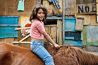 A little Colombian girl rides a horse in the 'Invasión', a temporary slum in Bogota, Colombia, 1 April 2006. The internal armed conflict in Colombia together with lack of social network caused appearence of small invasion slums in all Colombian urban zones in last years. These illegal settlements rise quickly in free uncontrolled spaces between industrial buildings, both in the city centres and peripheries. Shacks do not have sanitation network, neither electricity. Most of their inhabitants are war fugitives violently displaced from their original lands in the country by guerrilla or paramilitary forces. Picking up the rubbish and recycling it is a common survive strategy for people living in these temporal ghettos until those are not dismantled by city administration.