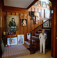 A collection of portraits on a wood panelled staircase include flea-market finds and works by Dan Witz and Alex Katz