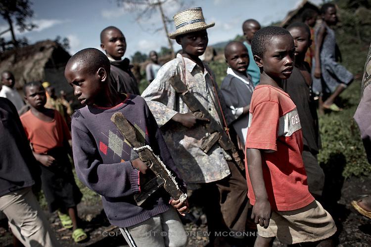Young boys carry wooden guns through the streets of Kichanga, North Kivu, DRC.