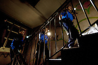 Switzerland. Geneva. Three police officers ( two policewomen and a policeman) holding flahlights in their hands climb at night the stairs searching for squatters, usually illegal migrants, sleeping inside the rooms of a derelict building. Squatting consists of occupying an abandoned or unoccupied area of a building - usually residential - that the squatter does not own, rent or otherwise have lawful permission to use. Three police officers are wearing a ballistic vest, bulletproof vest or bullet-resistant vest which is an item of personal armor that helps absorb the impact from knives, firearm-fired projectiles and shrapnel from explosions, and is worn on the torso. Soft vests are made from many layers of woven or laminated fibers and can be capable of protecting the wearer from small-caliber handgun and shotgun projectiles, and small fragments from explosives such as hand grenades. 10.05.12 © 2012 Didier Ruef..