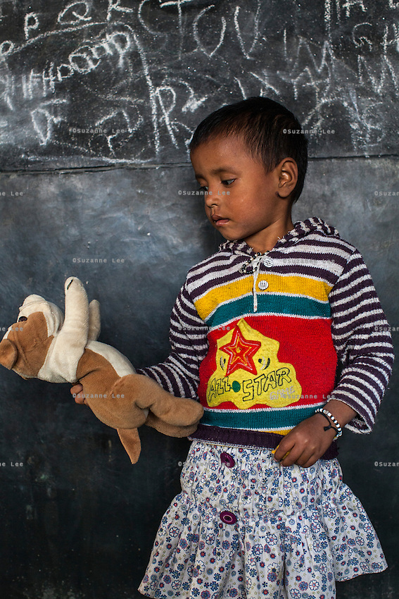 Sumitra, 3, poses for a portrait with a soft toy in the Guria Non-Formal Education center in the middle of the Shivdaspur red light district, Varanasi, Uttar Pradesh, India on 20 November 2013. Guria uses the soft toys as a form of therapy for the children of the women in prostitution and also use it as signals of the children's emotional wellbeing.