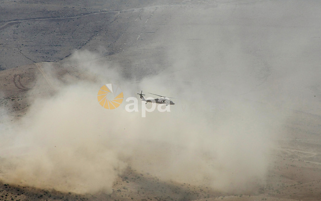 An Israeli military helicopter flies over the Massafer Yatta area, near the West Bank City of Hebron, on 01 October 2013. According to reports, Palestinian citizens in the area south of Yatta must leave while Israeli government claims that all eight villages in a so-called 'Firing Zone 918' were merely temporary seasonal residences when the area was declared a closed military zone for training in 1980. The villagers say they have been living there permanently since before Israel's establishment in 1948. Photo by Mamoun Wazwaz