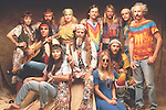 Twelve hippies pose for the camera.