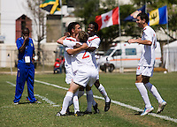 Sadi Jalali (9) of Canada celebrates his goal with teammates Samuel Piette (2) , Chris Nanco (11),  and Ismail Benomar (4) as the Barbados head coach Kenville Layne looks on during the group stage of the CONCACAF Men's Under 17 Championship at Jarrett Park in Montego Bay, Jamaica. Canada defeated Barbados, 8-0.