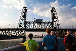 Touring the Willamette River by small ship, passengers watch as the lower part of the Steel Bridge is raised to allow the National Geographic Sea Lion pass