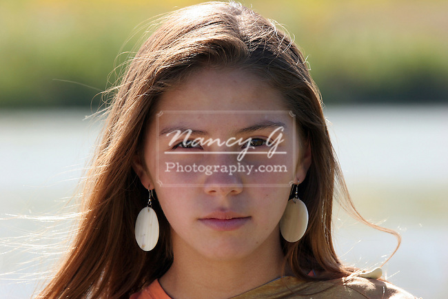 young Native American Indian teenager girl walking along a rivers ...