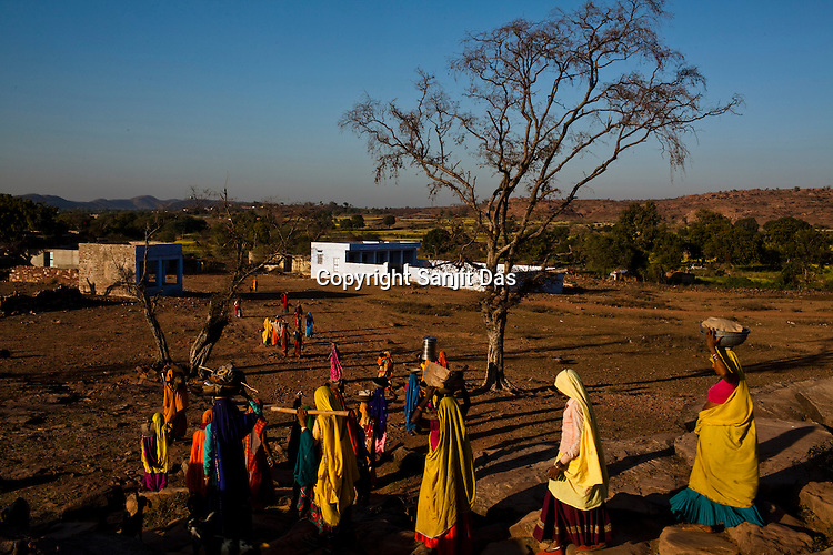Women return back home after working at the Gobra Ki Nari Mein site near the Khori Bijasan Devi Temple in Karauli district of Rajasthan, India. The National Rural Employment Guarantee Act (NREGA) that has created a source of additional income for families living below the poverty line by providing a minimum 100 days of employment assured under the Act. Photo by Sanjit Das