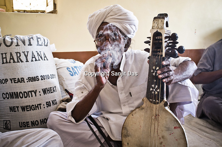 75-year-old Manganiyar artist, Saqar Khan takes a break and smokes a biri (local cigarette) inbetween field recordings inside his house in Hamira village of Jaiselmer district in Rajasthan, India. Photo: Sanjit Das/Panos