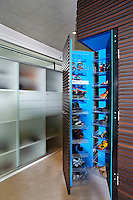 A cleverly designed built in wardrobe opens to reveal a bold, blue interior and plenty of storage space for shoes. Other storage cupboards are concealed behind opaque glass.