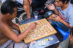 Vietnamese men smoking and arguing over a game of XiangQi, or Chinese chess, on the streets of Hanoi.