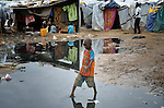 A boy navigates a flooded portion of a camp for internally displaced families located inside a United Nations base in Juba, South Sudan. The camp holds Nuer families who took refuge there in December 2013 after a political dispute within the country's ruling party quickly fractured the young nation along ethnic and tribal lines. The ACT Alliance is providing a variety of services, including fresh water, sanitation and refuse collection services, to the more than 20,000 people living in the camp.