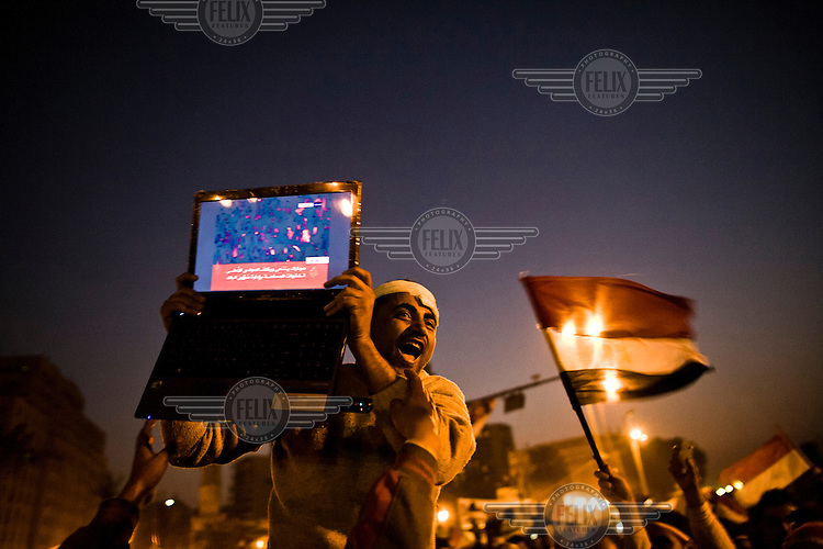 A joyful man displays a laptop showing the Al Jazeera news channel's coverage of the resignation of President Mubarak. At around 6pm on 11 February 2011 news of Hosni Mubarak's immediate resignation filtered through to the crowds camped out in Tahrir Square sparking wild celebrations. 25 January 2011 saw the beginning of a nationwide 18 day protest movement that eventually ended the 30-year rule of Hosni Mubarak and his National Democratic Party.