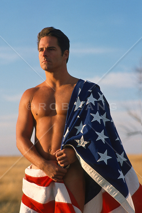 Naked good looking man wrapped in an American flag