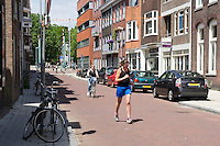 In Utrecht is een jonge vrouw met een koptelefoon in haar oren midden op straat aan het hardlopen.<br /> <br /> In Utrecht a young woman is running in the streets.