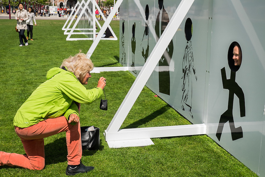 Nederland, Amsterdam, 30 mei 2015<br /> Publiek amuseert zich met het kunstwerk van Liam Gillick op het Museumplein. <br /> Op uitnodiging van het Stedelijk Museum en het Holland Festival heeft de Britse kunstenaar Liam Gillick een grote installatie op het Museumplein geplaatst. Aan het werk, getiteld All-Imitate-Act, kan iedere voorbijganger deelnemen: de installatie bestaat uit een reeks panelen, met in ieder paneel een gat waar een gezicht doorheen past. De voorstellingen op de panelen ontleende Gillick aan de grafische collectie van het Stedelijk Museum. Wie zijn gezicht door het gat steekt en zich laat fotograferen wordt zo onderdeel van de geschiedenis en de collectie van het Stedelijk Museum.<br /> <br /> Foto: Michiel Wijnbergh