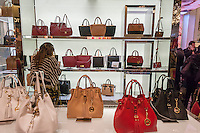 "A shopper browses Michael Kors handbags in the Macy's Herald Square flagship store in New York looking for bargains on the day after Thanksgiving, Black Friday, November 28, 2014. Many retailers, including Macy's, opened their doors on Thanksgiving evening extending the shopping day and giving Thanksgiving the nickname ""Gray Thursday"". (© Richard B. Levine)"