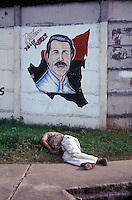 Drunken man passed out in fron of a mural showing Sandinista leader Daniel Ortega in a poor neighbourhood of Managua, Nicaragua