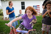 """Emily Rouse, left, wife of Jason Rouse and their children Willie Rouse, 6, back left, Elizabeth Rouse, 8, center, and Lydia Rouse, 9, right, chat outside their home on Monday, July 27, 2015 in Cumberland, Iowa. Rouse is in his second year of using Farmobile to collect data and information on his farm. """"Once you get an idea of what you got you're able to change things and Farmobile allows us access to that anytime,"""" he said. Rouse said it allows him to fine tune or make decisions on what he needs to change or improvise. """"It paints a picture of the whole field as you're overlooking it,"""" he said."""