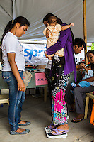 A lactating mother weighs herself and her baby as she registers to receive SPRINT-IPPF dignity kits and other reproductive health (RH) information at a RH Medical Mission in the Taluksangay Barangay Hall, Zamboanga, Mindanao, The Philippines on November 5, 2013. These Internally Displaced People (IDP) had taken refuge in this Barangay (neighbourhood) after surviving the 3 week long attack by MNLF rebels. Photo by Suzanne Lee for SPRINT-IPPF