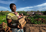 Modolasi Mkhondya carries bricks for her new house in Karonga, a town in northern Malawi where the ACT Alliance has worked with local residents to recover from a 2009 earthquake.