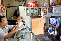 Thailand. Bangkok. A father and his son, nine months old. seat and watch television in the shophouse, which provides business in wholesale, retail and service sectors. The family of chinese origin has been living in Tha Tian for a century. Tha Tian is a community located in the downtown area and in the center of the urban historic district, called Koh Rattanakosin. 01.04.09 © 2009 Didier Ruef