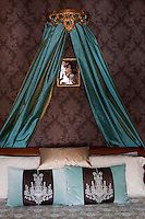 A gilt corona with blue silk drapes is set above a double bed dressed with cushions and blue pattern bedcover. The rich blue contrasts with the deep plum colour of the wallpaper.