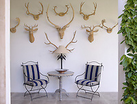At one end of the covered terrace a collection of sculptures mimicking old-fashioned hunting trophies are displayed above a pair of wrought-iron garden chairs