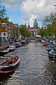 Amsterdam, Holland. Looking down a canal towards St. Nicholas church.  The impression is one of business and beauty.